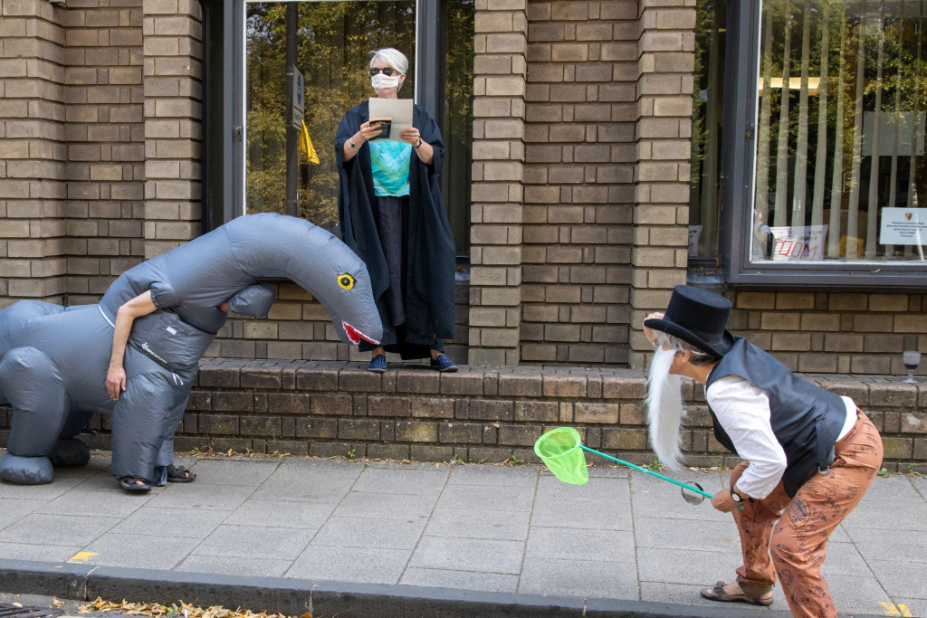 Outside a brick building Yoga wears an inflatable grey dinosaur suit, a lady in academic robes reads a proclamation, someone dressed in a fake beard and top hat approaches Yoga with a small butterfly net.