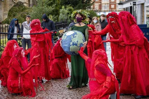 A group of red rebels reach out as a woman dressed in green, with a wreath of leaves around her head is dragged through the street with a rope around her neck.  The woman holds a large earth in front of her as she walks