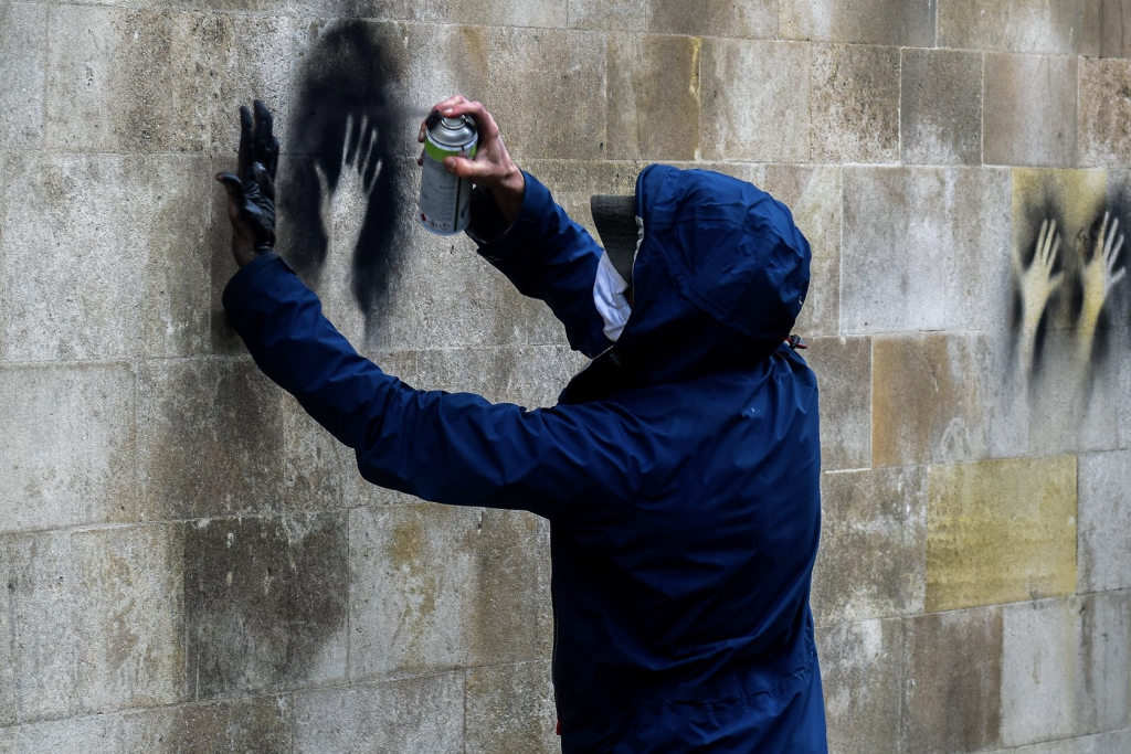 A man in a blue boiler suit stretches out his hand against an old stone walled building.  He is using his hand and black chalk paint to create outlines of his hand against the stone.