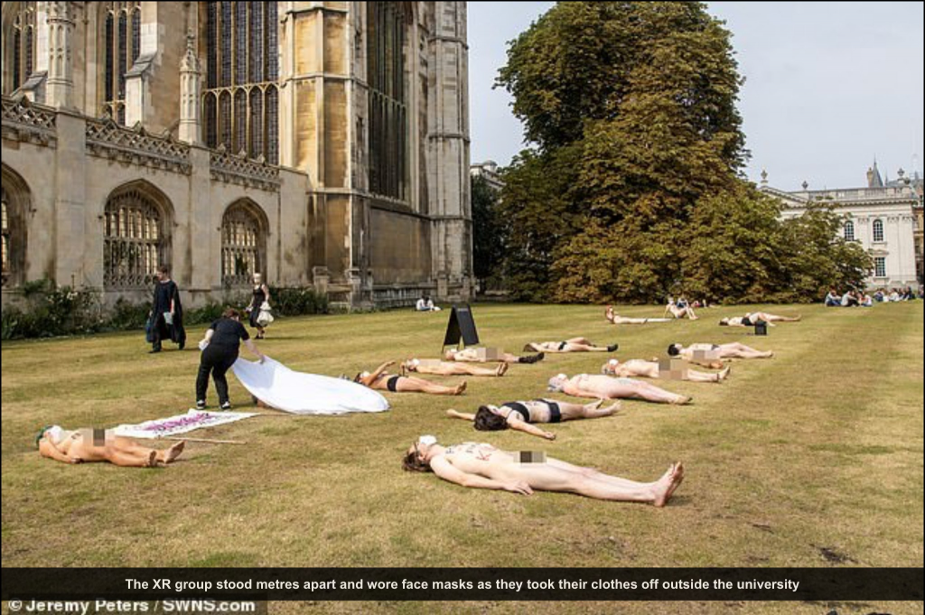 Outside an impressive stone building (Kings College, Cambridge) a group of people lie naked and semi naked on the grass as if they are corpses.  Someone is covering the people on the ground with a white sheet.