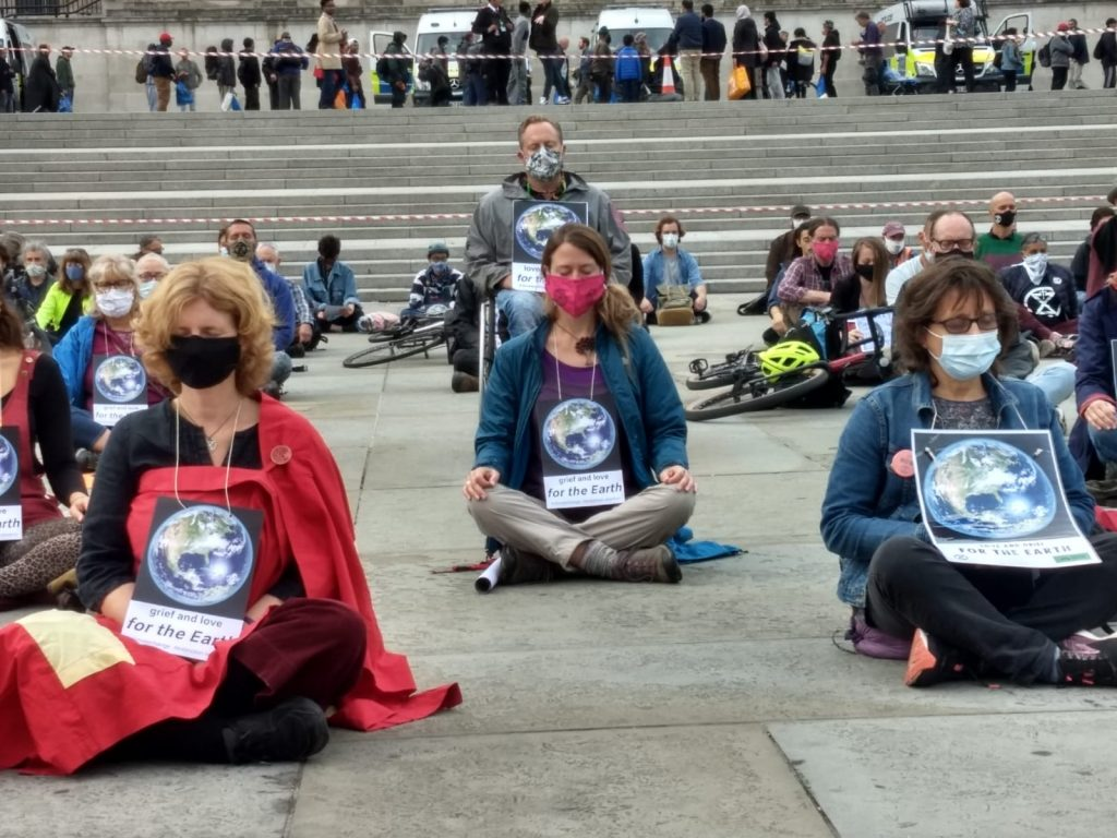 Rebels meditating in Trafalgar Square, wearing placards which say 'In grief and love for the Earth'