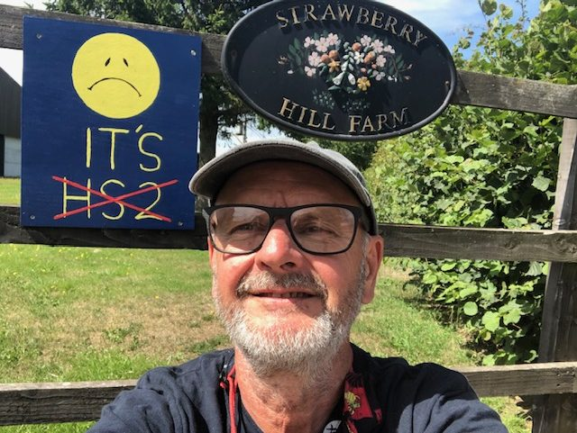 Paul standing in front of a wooden gate which has a sign on it which says 'Strawberry Hill Farm' and another which has a sad face and HS2 crossed out.