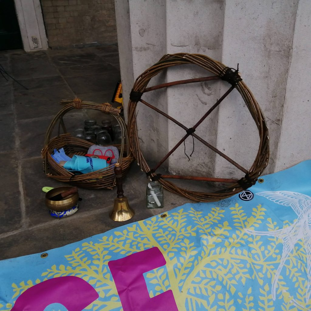 A wicker XR sign, part of an XR banner, a candle in a jar, a bell, and a Buddhist bowl.