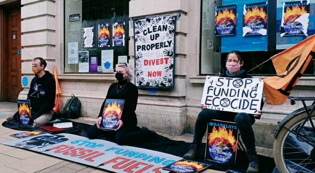 Three people meditating outside a Barclays bank in Cambridge. They have pasted lots of 'the ecocide bank' posters to the windows and have signs and banners including: Stop Ecocide funding, clean up properly divest now and stop funding fossil fuel.
