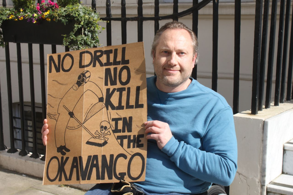 Male activist in a blue jumper, outside a building with black railings. He holds up a sign which says 'No Drill, No Kill, in the Okavango'.
