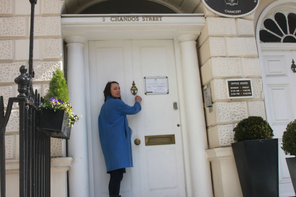 An activist in a blue coat knocks on the door of an old expensive building to deliver a letter.