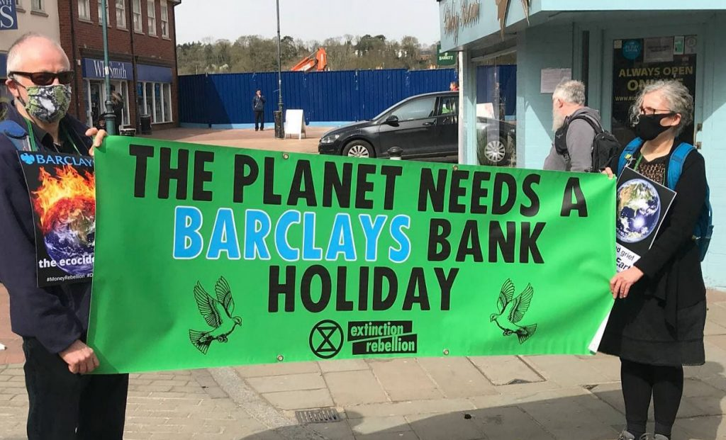two XR rebels hold a green banner with the words: the planet needs a Barclays bank holiday