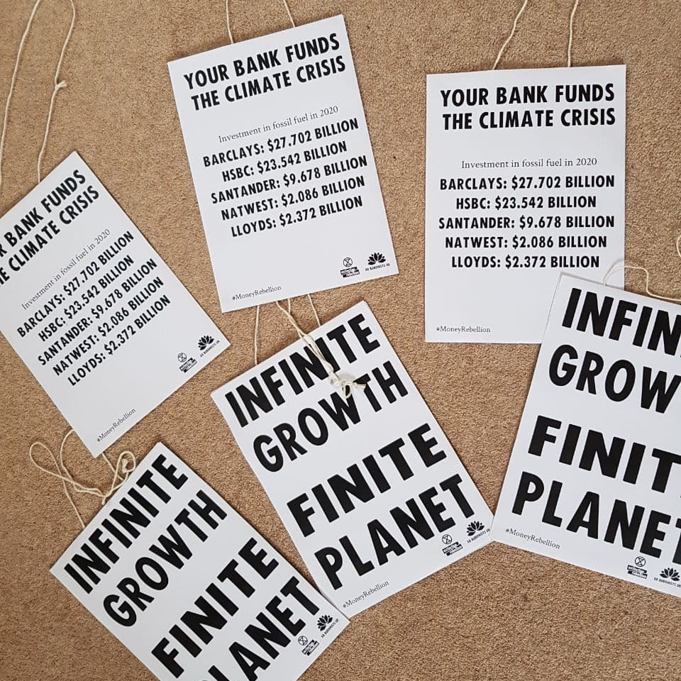 Placards reading Infinite Growth, Finite Planet, and Your Bank Funds the Climate Crisis.