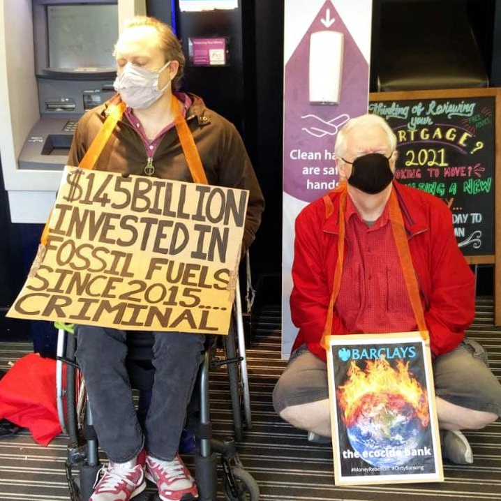 Nick and Patrick meditate in Barclary bank. 'Nick is wearing a sign that reads $145 Billion invested in fossil fules since 2015.. criminal.' Patrick is wearing a sign that says 'Barclarys the ecocide bank'