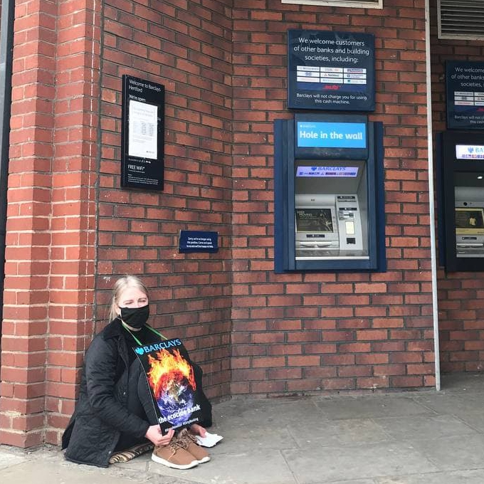 a person sits outside a Barclays bank, near and ATM, wearing an Barclays the Ecocide Bank placard.
