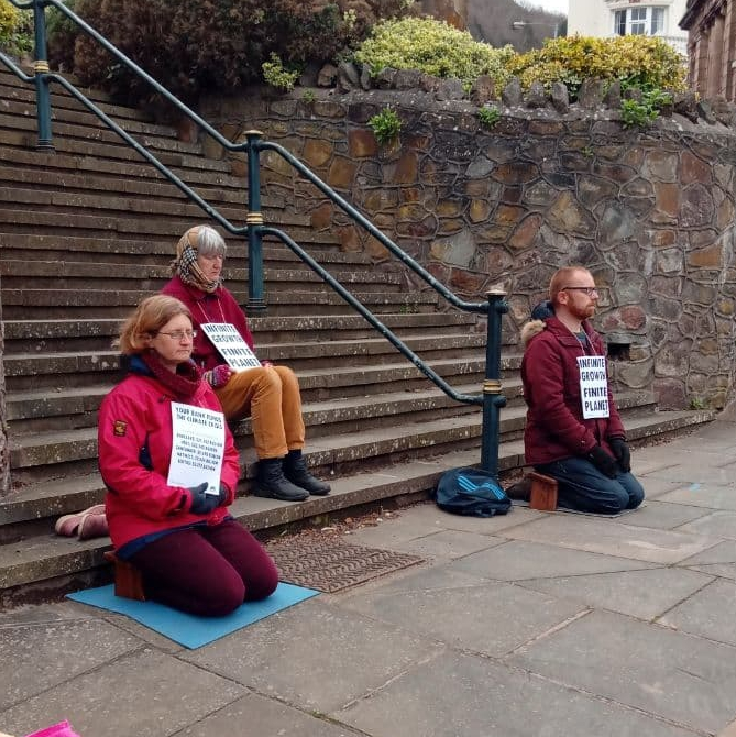 three meditators sit in front of some wide concrete steps wearing signs saying 'infinite growth finite planet' and listing high-street banks investment in fossil fuel in billions on dollars in 2020.