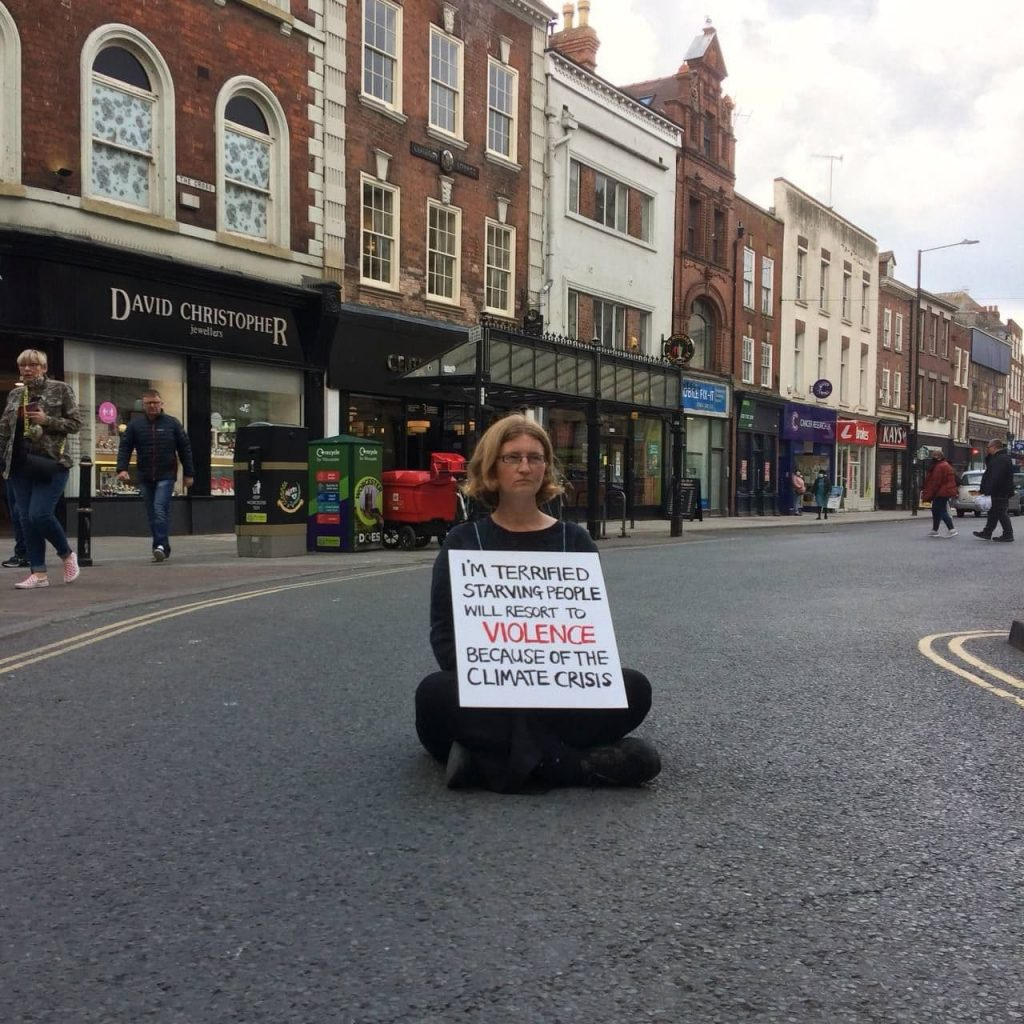 Satya sitting in the middle of a road, wearing a sign that says I am terrified of starving people resorting to violence because of the climate crisis