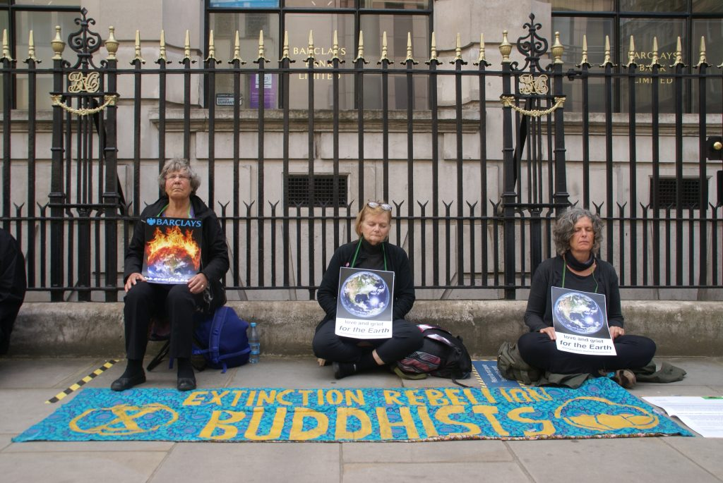 Three people sitting outside Barclays. There is a banner reading XR Buddhists on the ground.