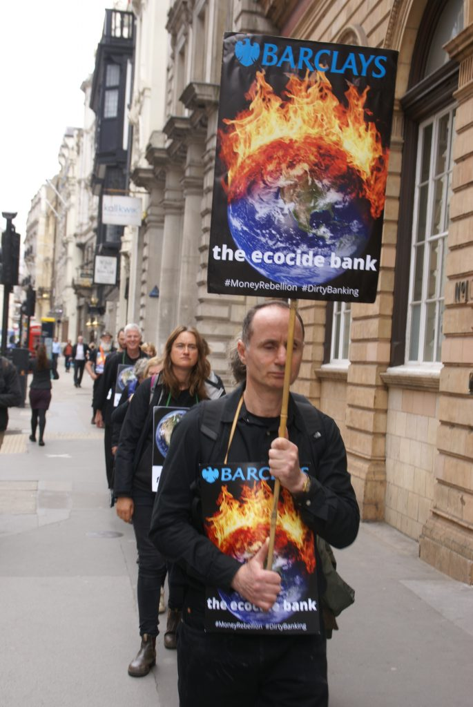 A line of people in walking meditation. The person at the front holds a sign reading Barclays the Ecocide Bank.