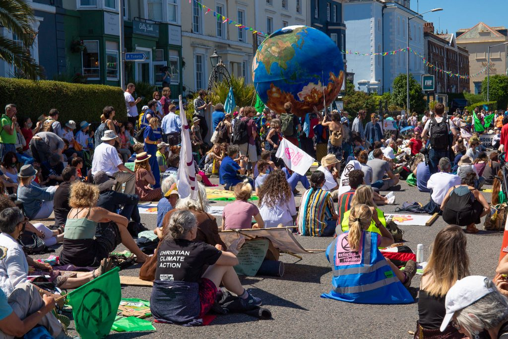 a crowd of protestors sitting in the road. Some demonstrators are carrying a large paper mache globe