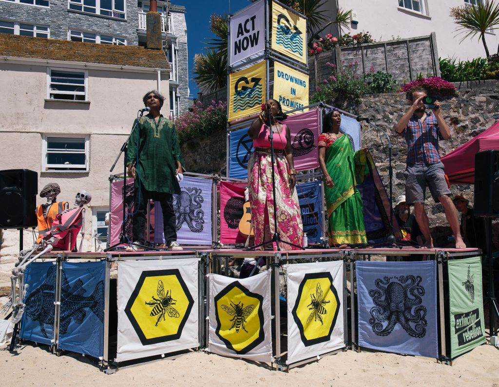 four people standing on a stage made from cubes of scaffolding decorated with large colourful squares, on the beach
