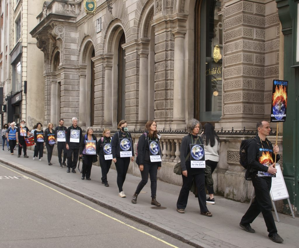 a line of people wearing black, wearing signs which read 'Barclays the Ecocide Bank', and 'In Love and Grief for the Earth'.
