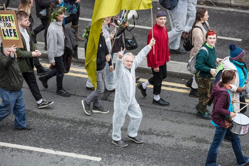 a crowd of people are walking on the road. One man dressed in a white 'forensic suit' is carrying a yellow flag and making the v for victory sign with his other hand