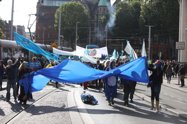 A group of people marching in the street. Front and centre a wide blue flag that stretches across the whole street. Other people are carrying blue flags and white flags.