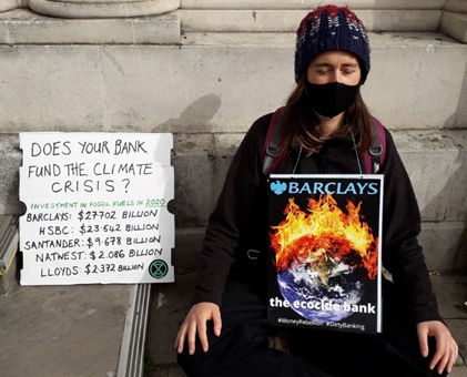 A person dressed in black sits in meditation wearing a placard which reads: Barclays the ecocide bank.  Next to her is a sign asking: Does your bank fund the climate crisis and listing the amount invested in carbon by banks in 2020  Barclays 27 Billion HSBC 23 Billion Santander 9 Billion Natwest 2 Billion Lloyds 2 Billion