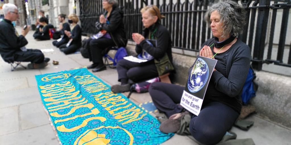 A line of people sitting in meditation posture, in black clothes, wearing 'in love and grief for the earth' placards.  Their hands are in anjali (the prayer gesture)